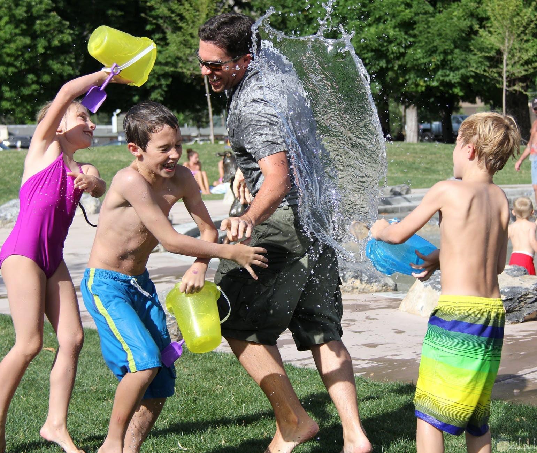 اطفال يستمتعون باللعب في المياه