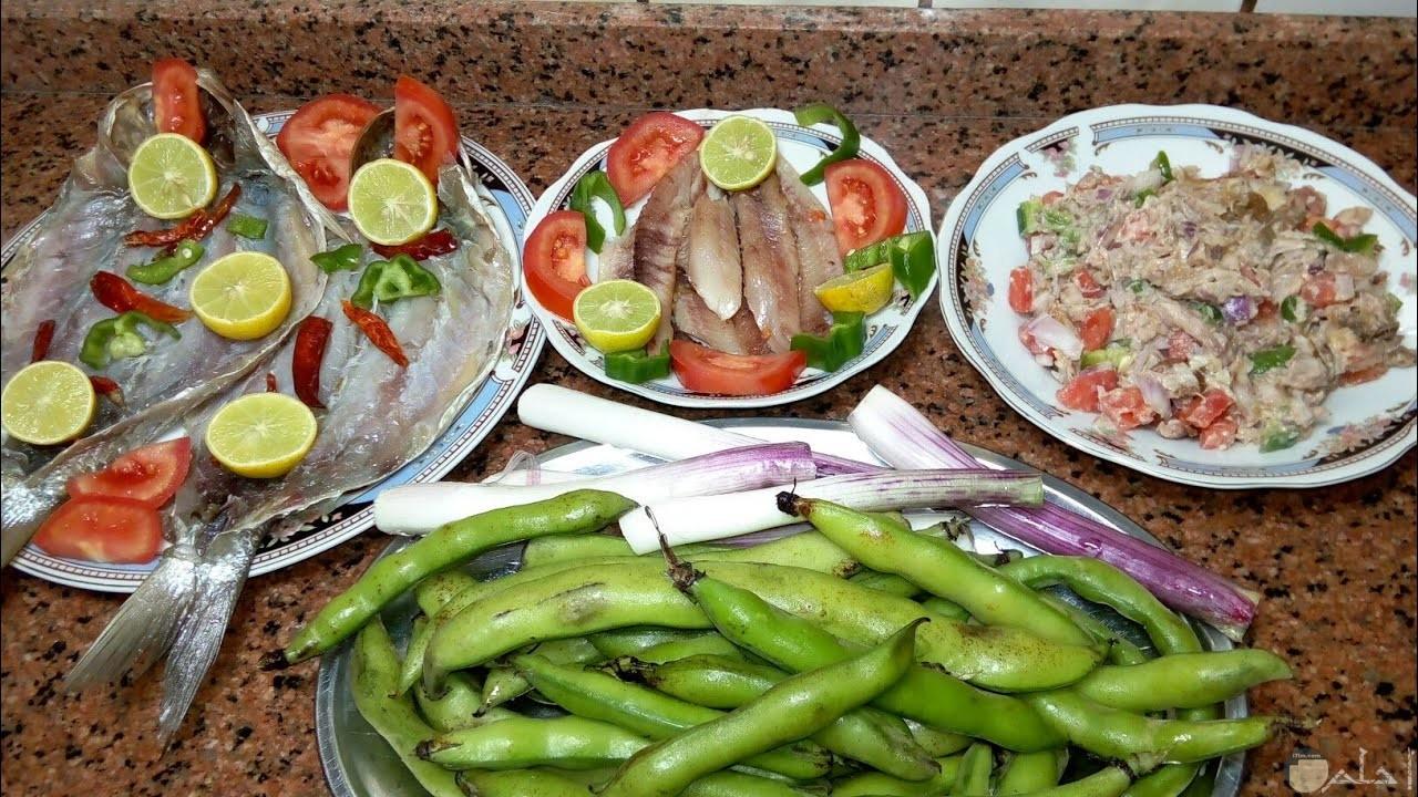 مجموعة اطباق فسيخ بجانبهم طبق فيه بصل جاهز للأكل