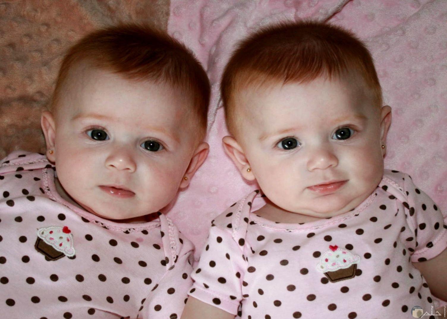 صورة لطفلين توأم جميلة يلبسون نفس الملابس باللون الوردي