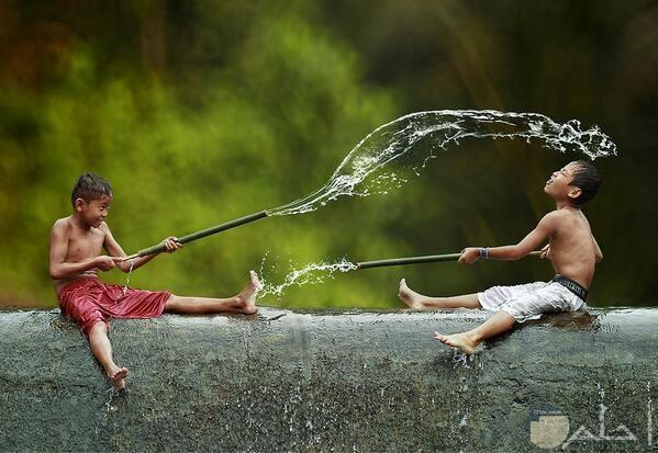 صورة أطفال واللعب بالماء ودقة تصوير القطرات