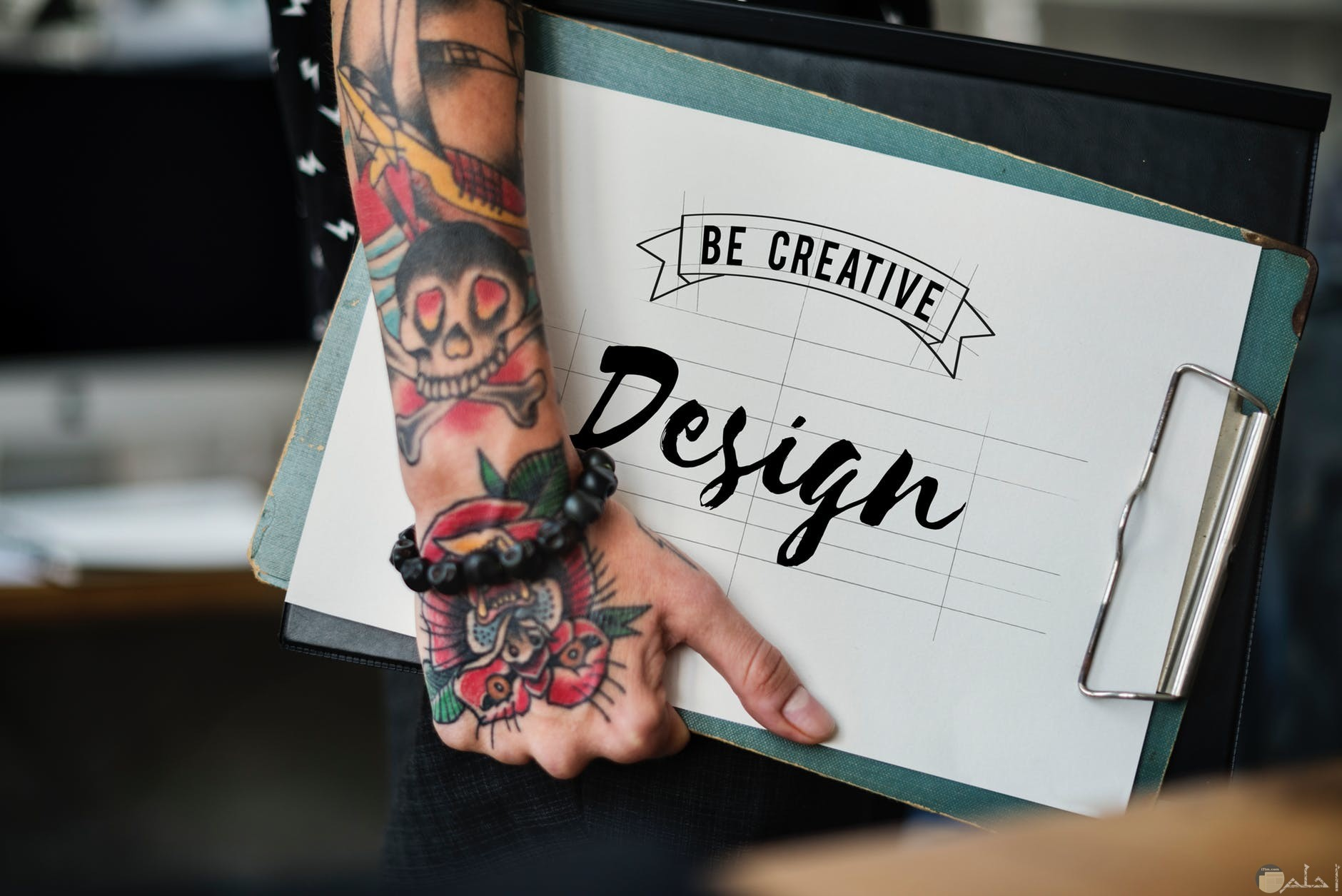 صورة يحملها شخص مدون عليها كلمة تصميم بالانجليزية