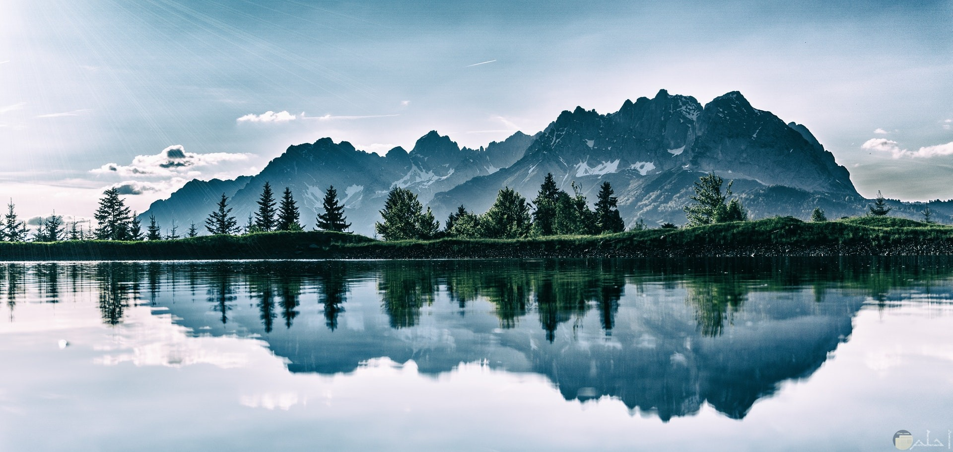 صورة مميزة للطبيعة تظهر الجبال والأشجار وإنعكاسهم في المياة بشكل جميل