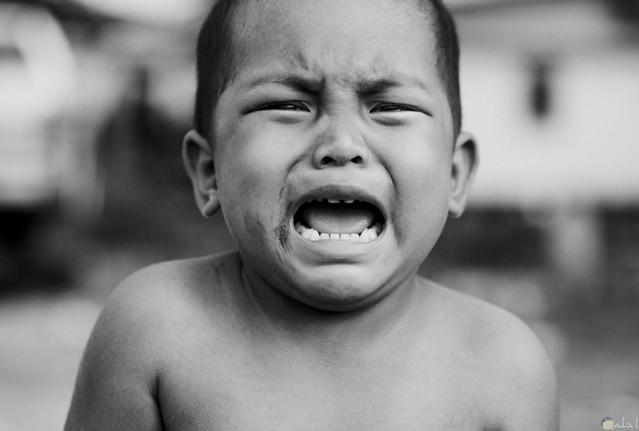صورة حزينة بالأبيض والأسود لطفل حزين ويبكي