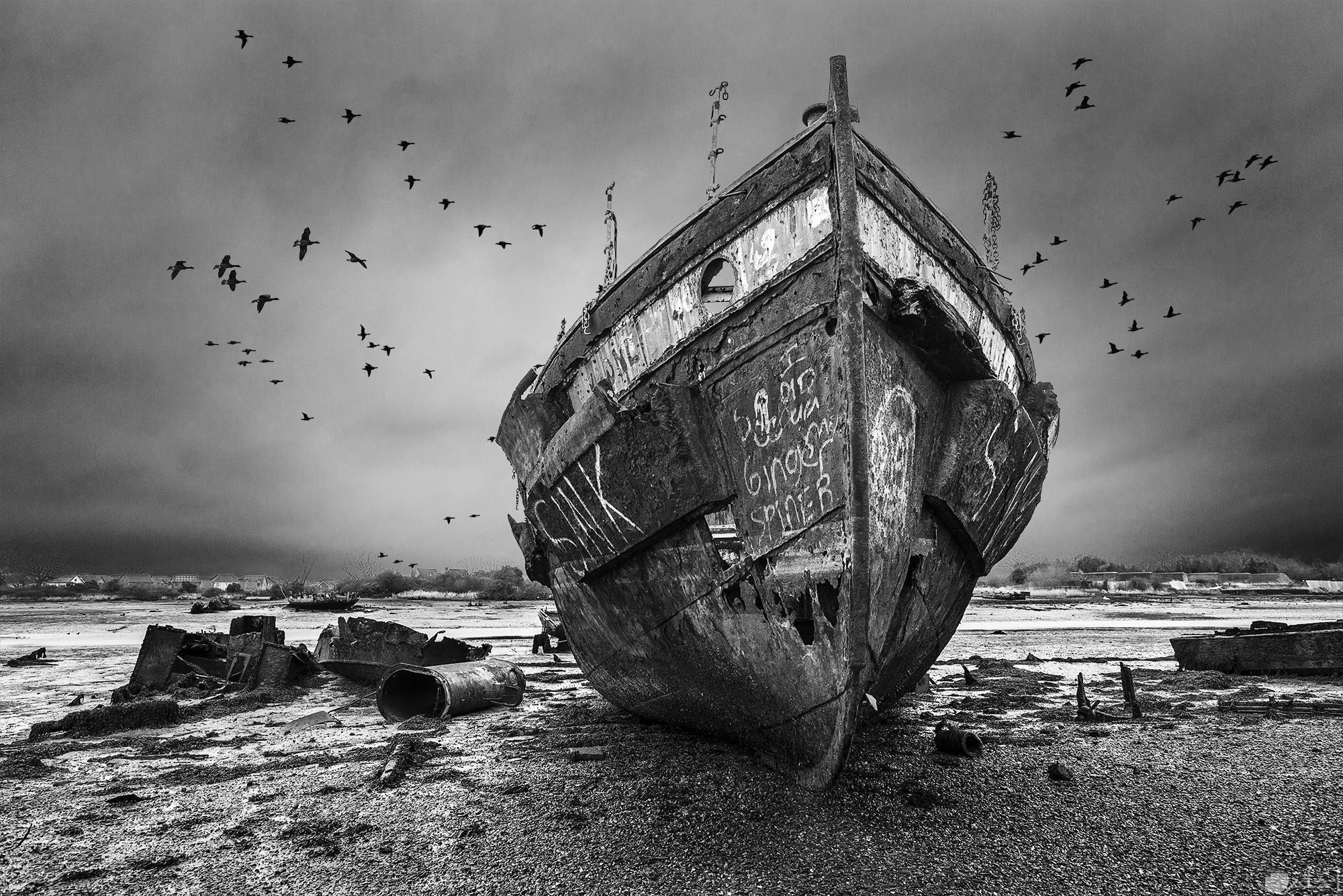 صورة حزينة بالأبيض والأسود لشكل مركب متهالك ومحطم