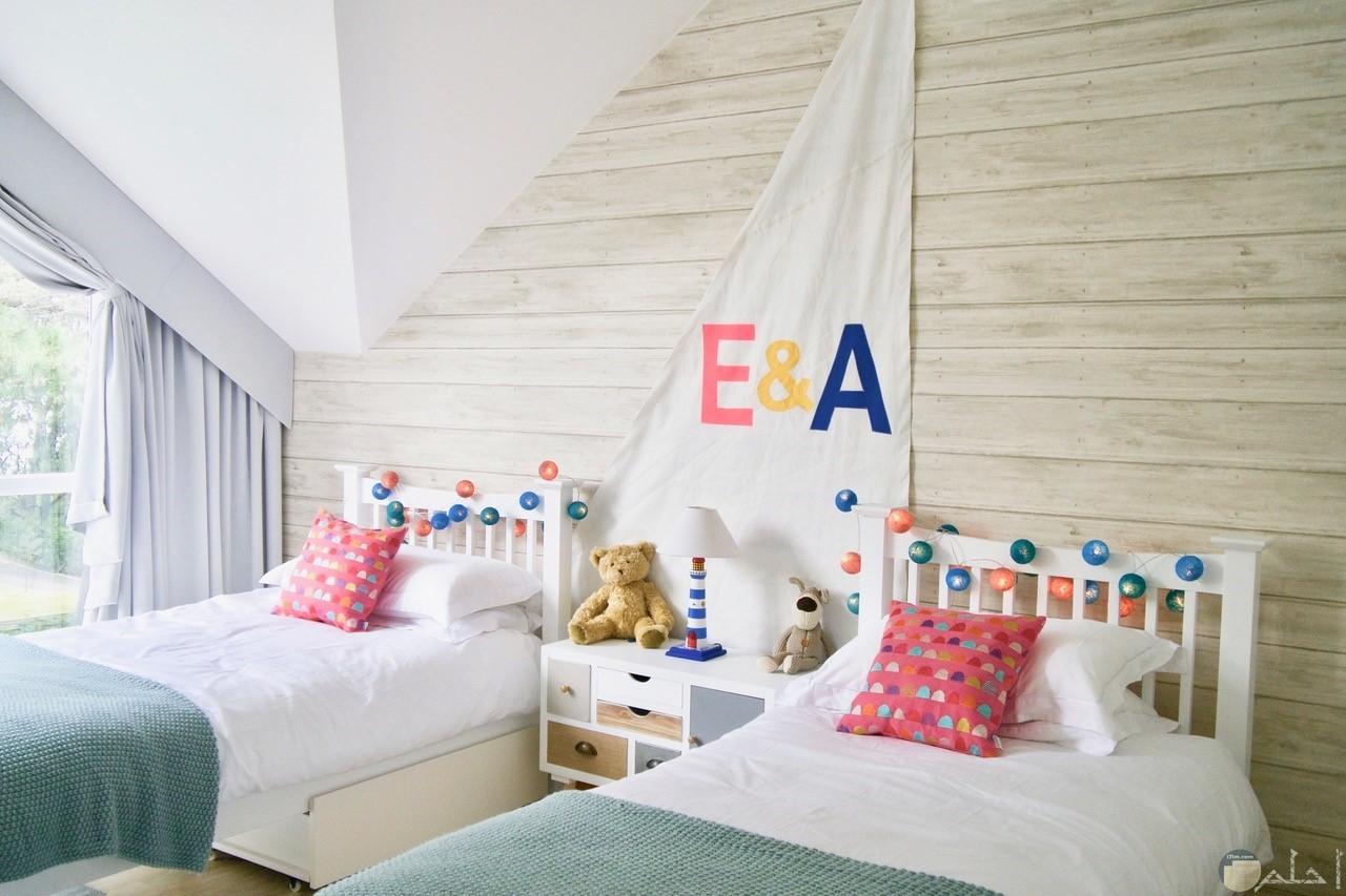 صورة جميلة لديكور غرفة أطفال بسريرين وبينهم احرف مميزة