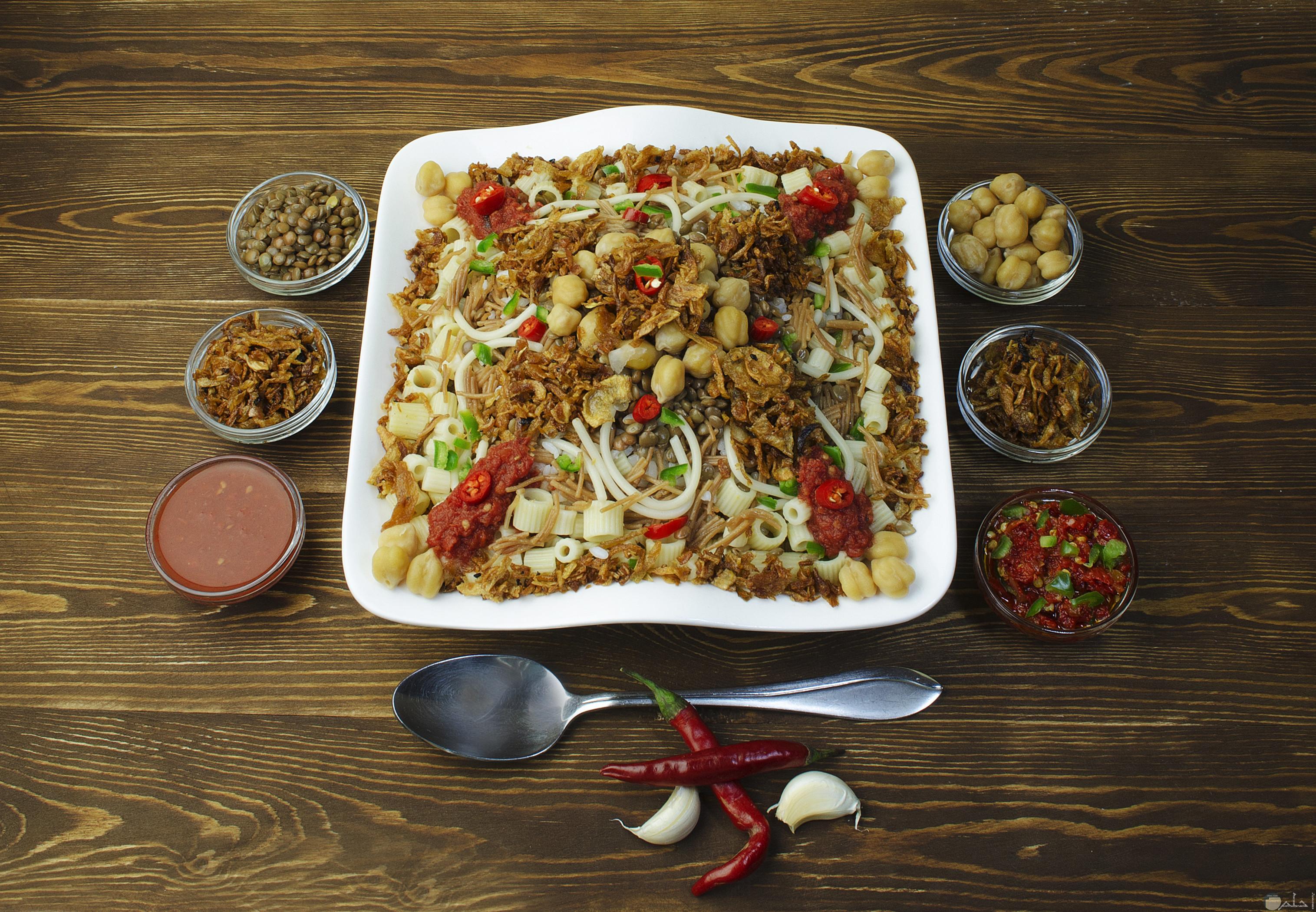صورة لطبق الكشري المصري بجانبه اطباق الشطه والصلصة والحمص