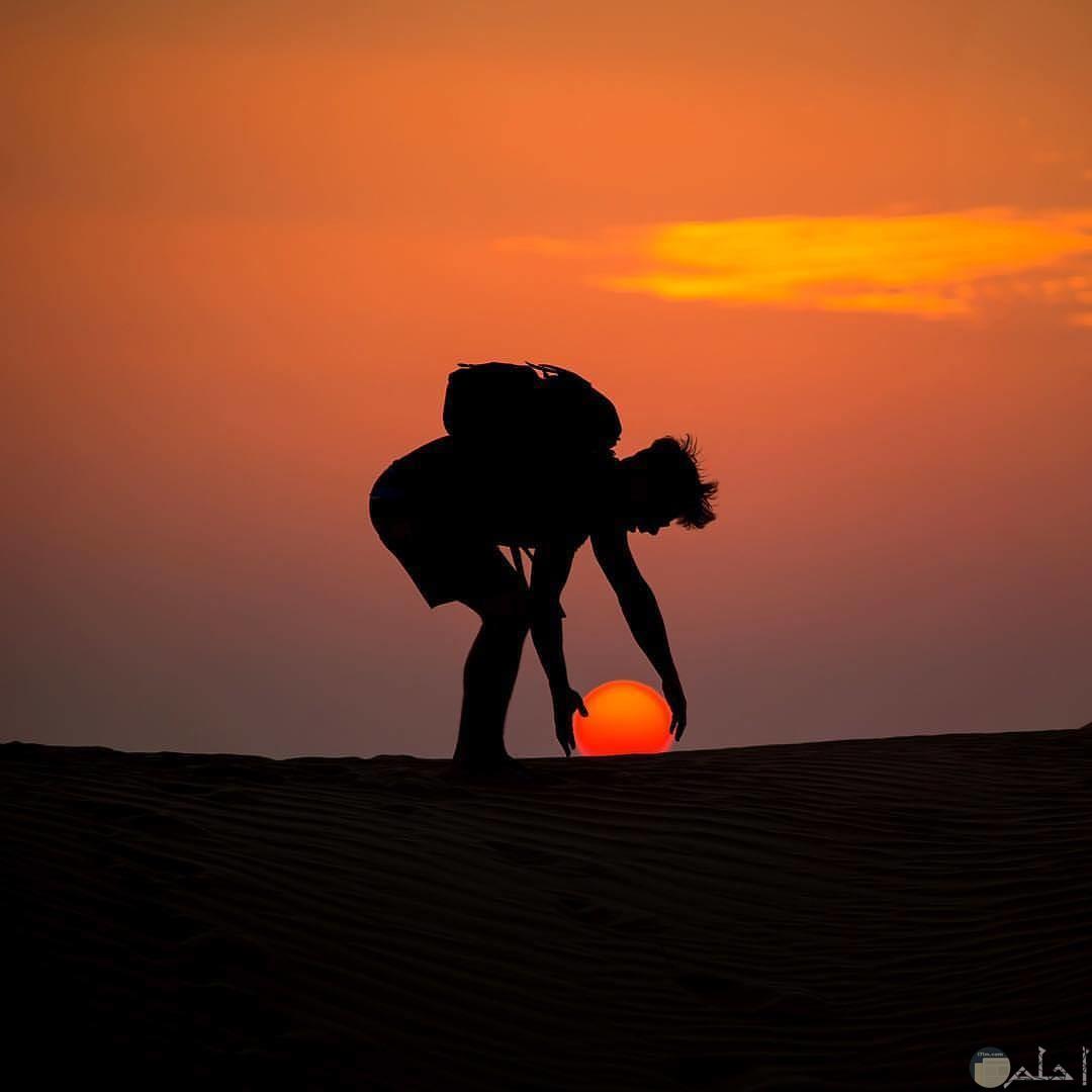صورة غريبة لغروب الشمس مع رجل يمسكها