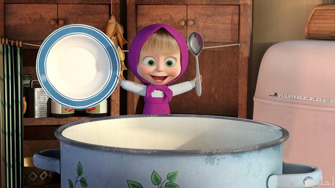 صورة لماشا وهي متحمسة للطعام وتمسك الملعقة والطبق