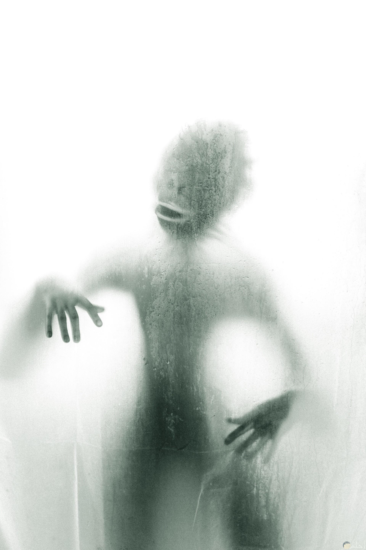 صورة مرعبة ومخيفة لكائن غريب خلف باب شبه شفاف