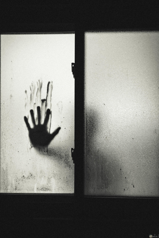 صورة مرعبة ليد علي زجاج مخيفة ورجل خلف الزجاج