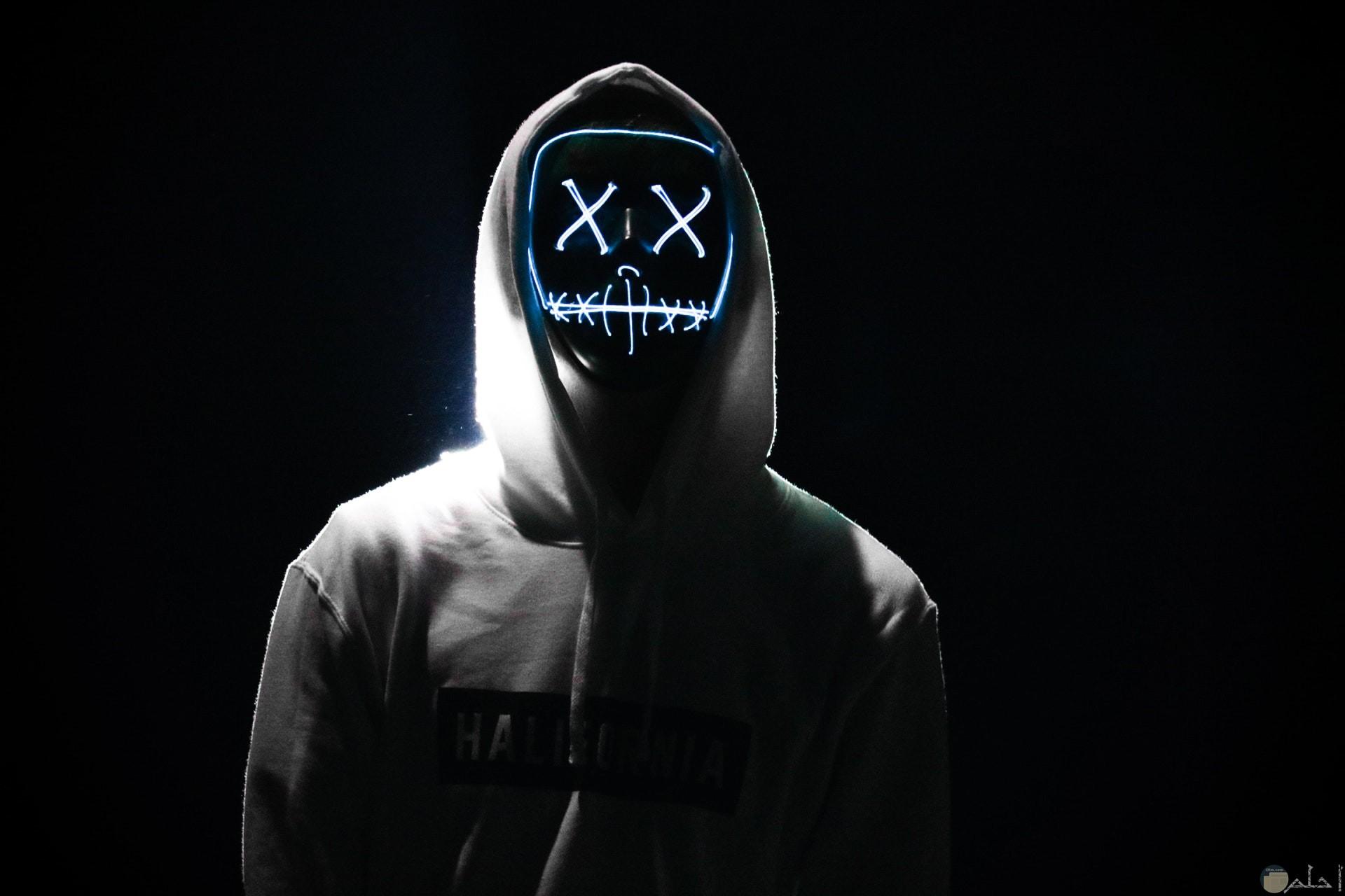 صورة مخيفة لإنسان يرتدي قناع مرعب مع خلفية سوداء