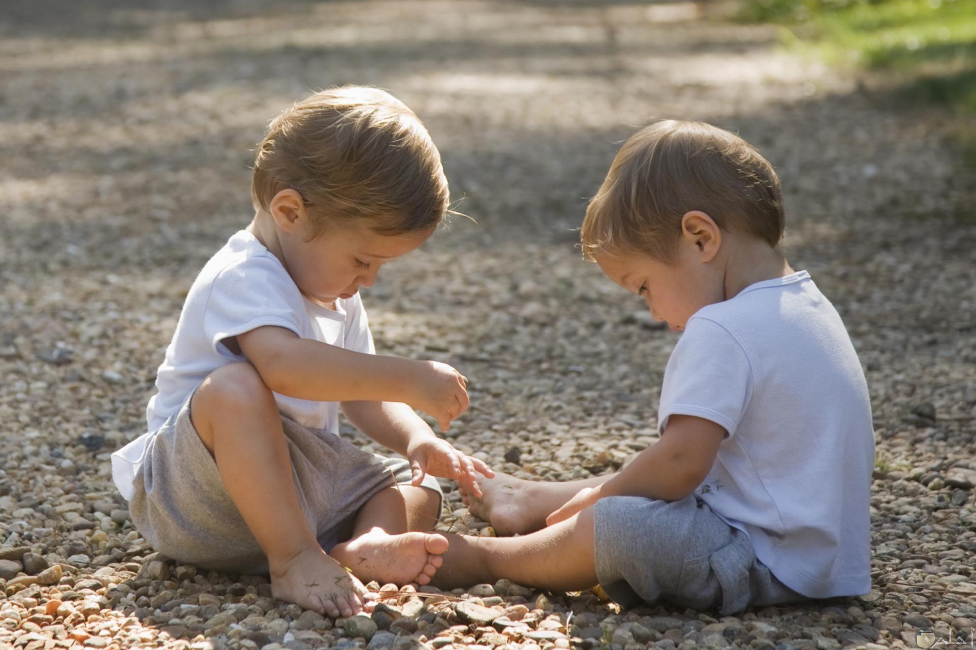 صورة جميلة لطفلين توأن يلعبون سوياً علي الأرض