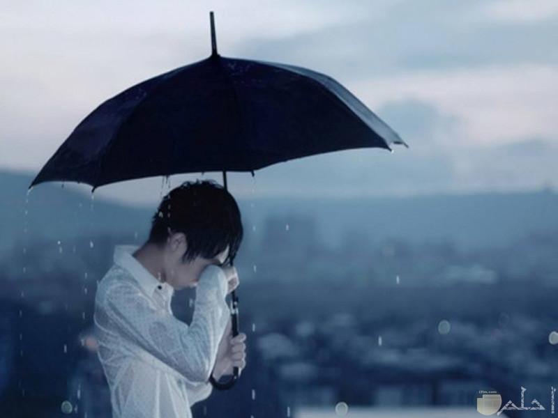 صورة لشاب حزين يبكي تحت المطر