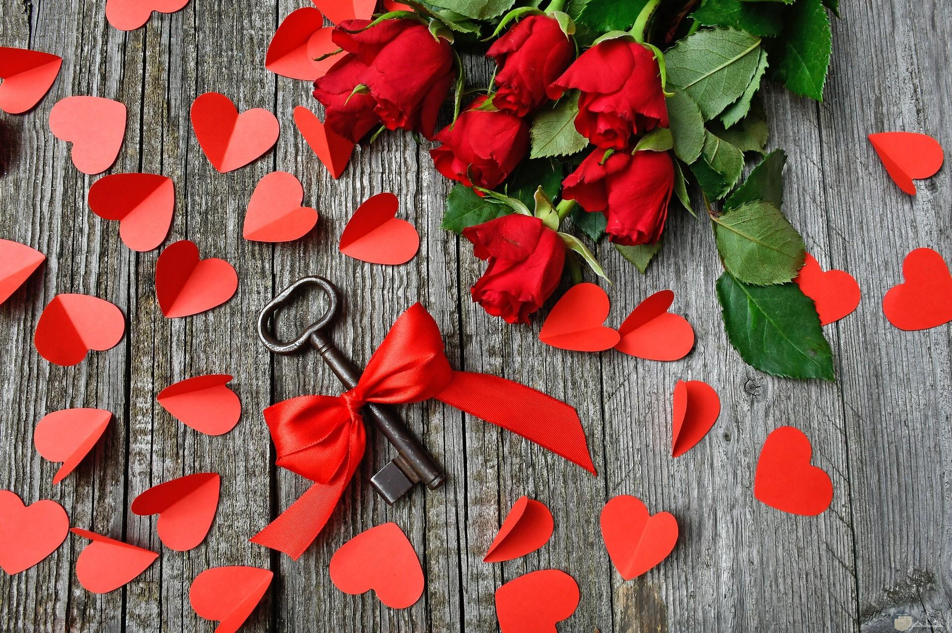 صورة لقلوب حمراء جميلة ورومانسية بجانبها ورود حمراءة رائعة