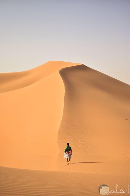 صورة لشخص يسير على جبل رمل