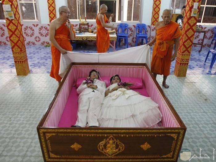 عروسان من تايلاند داخل تابوت في يوم زفافهما؛ لاعتقادهما أن ذلك سيبعد عنهما الحظ السيء، ويجلب السعادة.