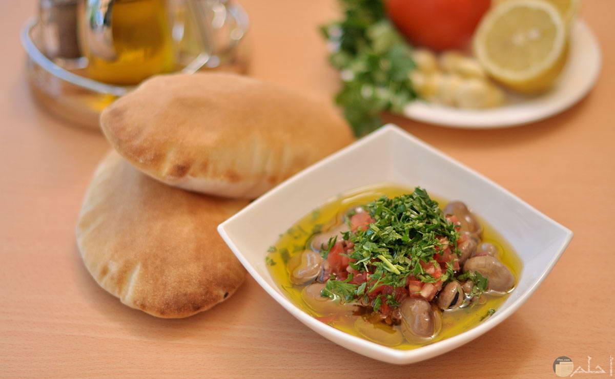 صورة لطبق الفول المصري علي مائدة بجواره باقي الأطباق والعيش