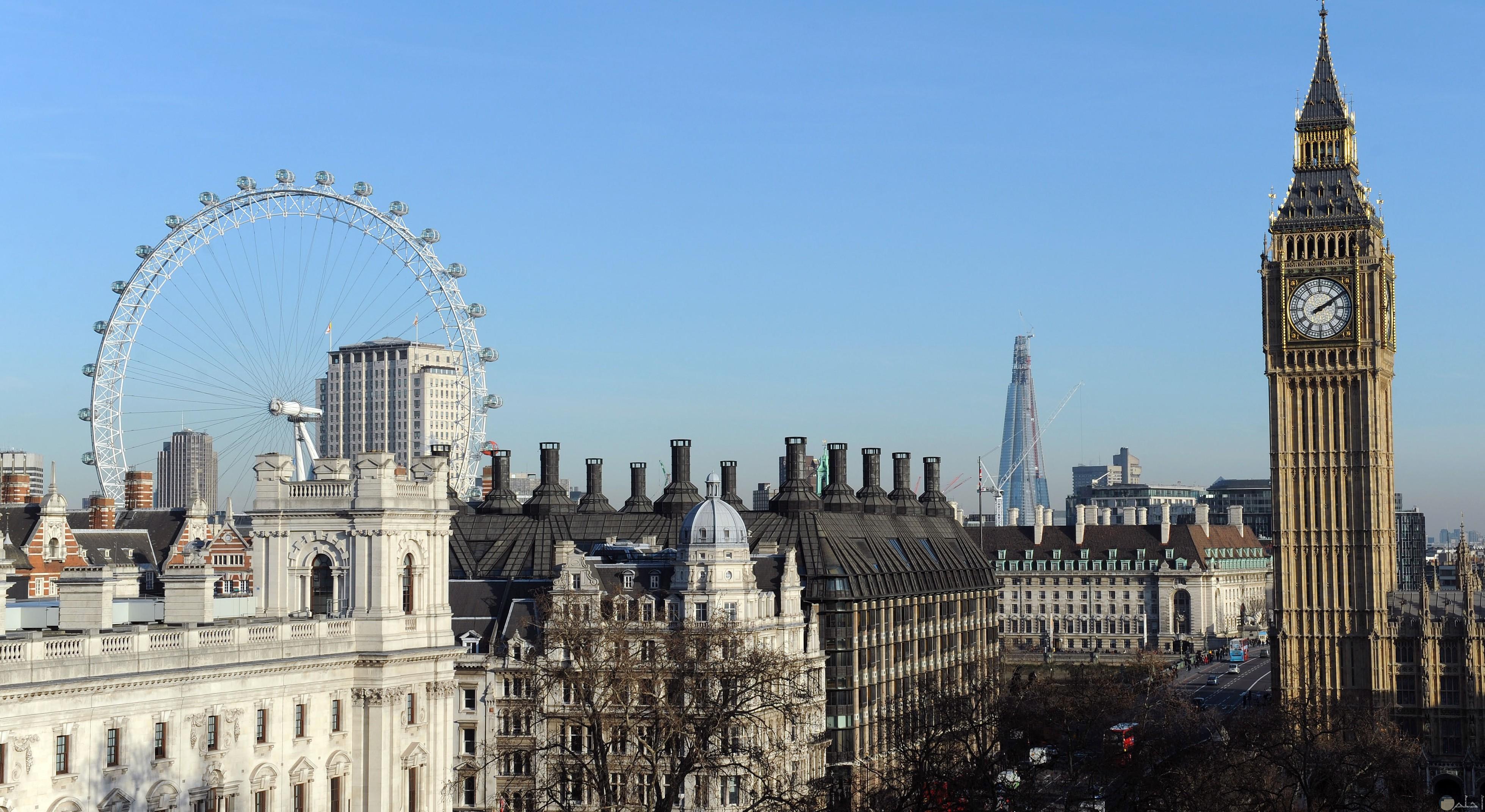 صورة تظهر الساعة المشهورة بلندن وعجلة عين لندن الضخمة بوقت النهار