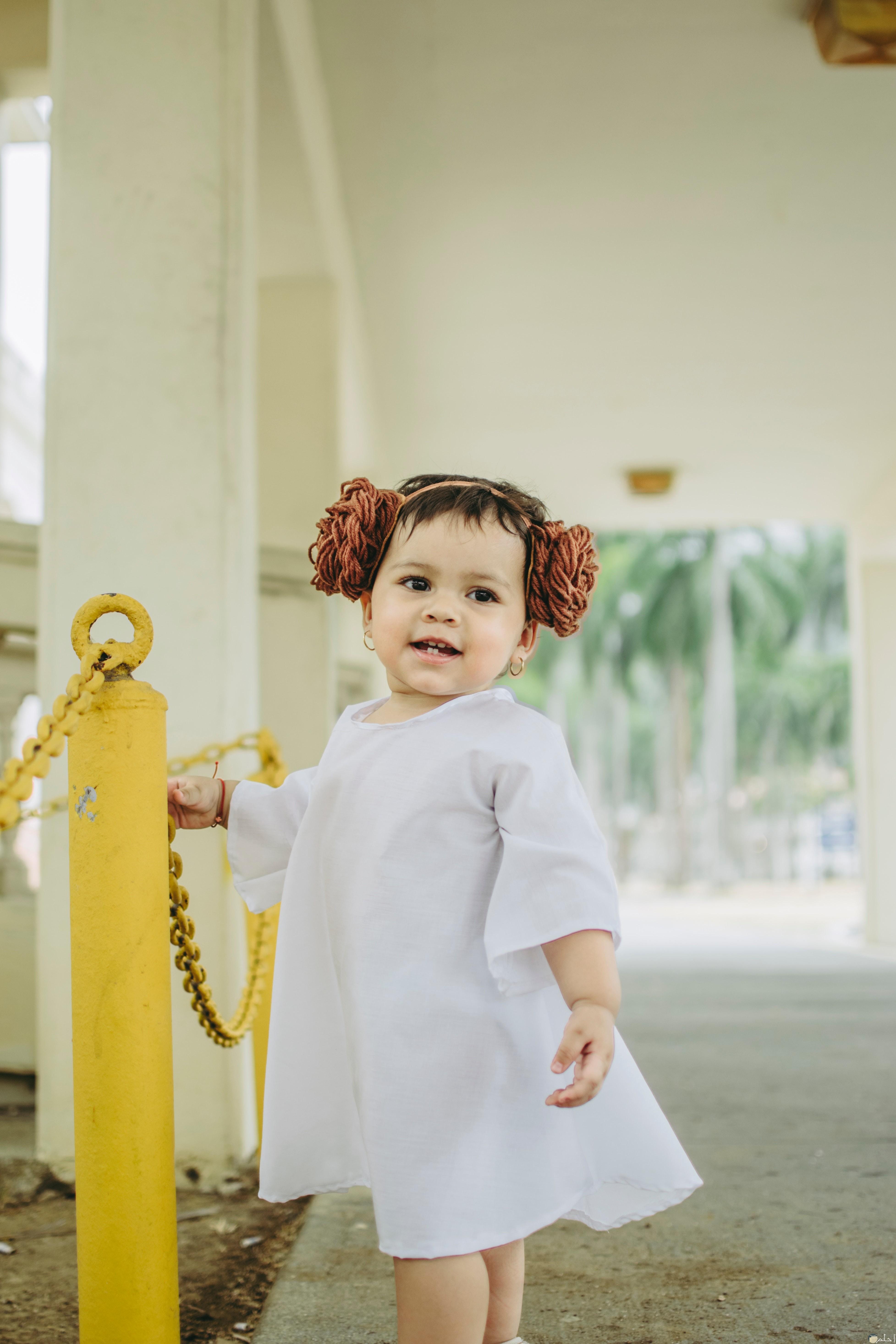 صورة طفلة ترتدى فستان ابيض قطن