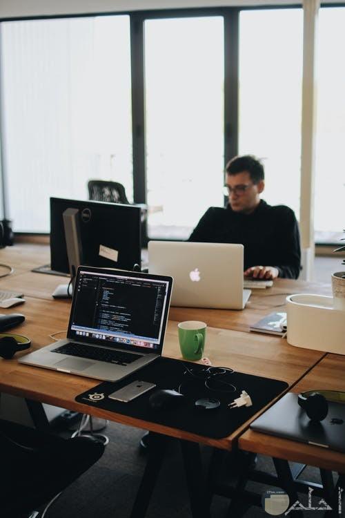 مكتب عمل يحتوي علي لاب توب وتكنولوجيا متطورة