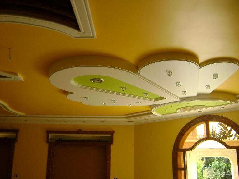 سقف بديكور جناح فراشه باللون الابيض ويدخل به اللون الاخضر الفاتح به كلوبات من النور ديكور خشب