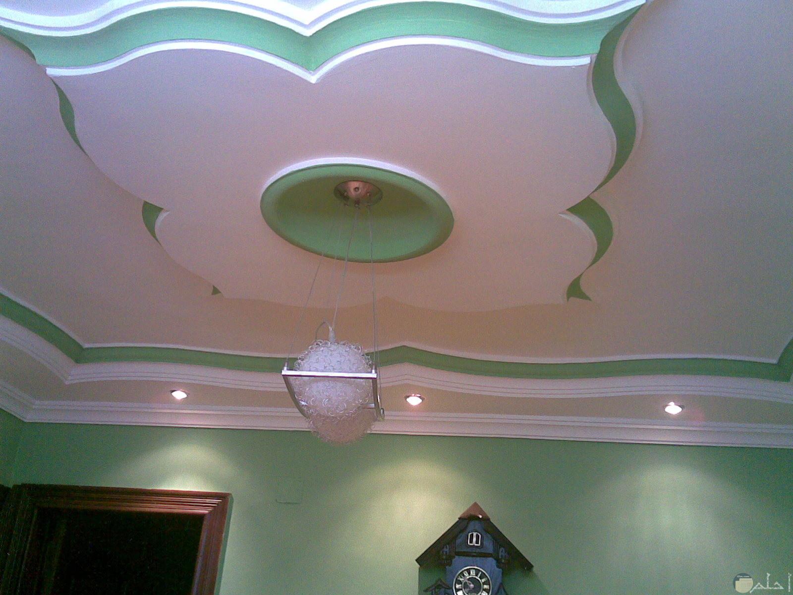 سقف من الاسمنت علي شكل ورده ابيض في اخضر وبالنصف نجفه بيضاء