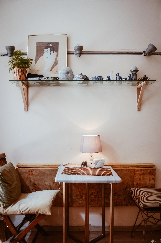 ديكور صغير وجميل كإضافة بالمنزل عبارة عن كرسين صغيرين امامهم طاولة صغيرة مع مصباح إضاءة مميز وفوقهم ستاند زجاجي عليه تحف جميلة