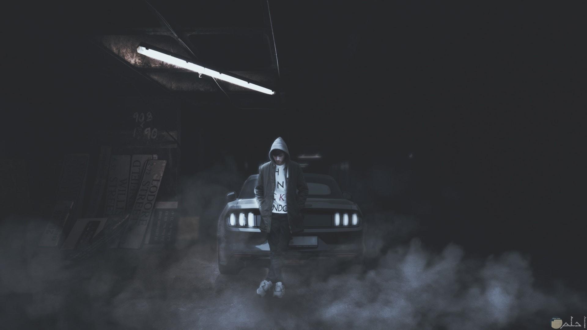 صورة أكشن رعب فيها شاب خلفه سيارة بمكان مهجور مع دخان بالمكان