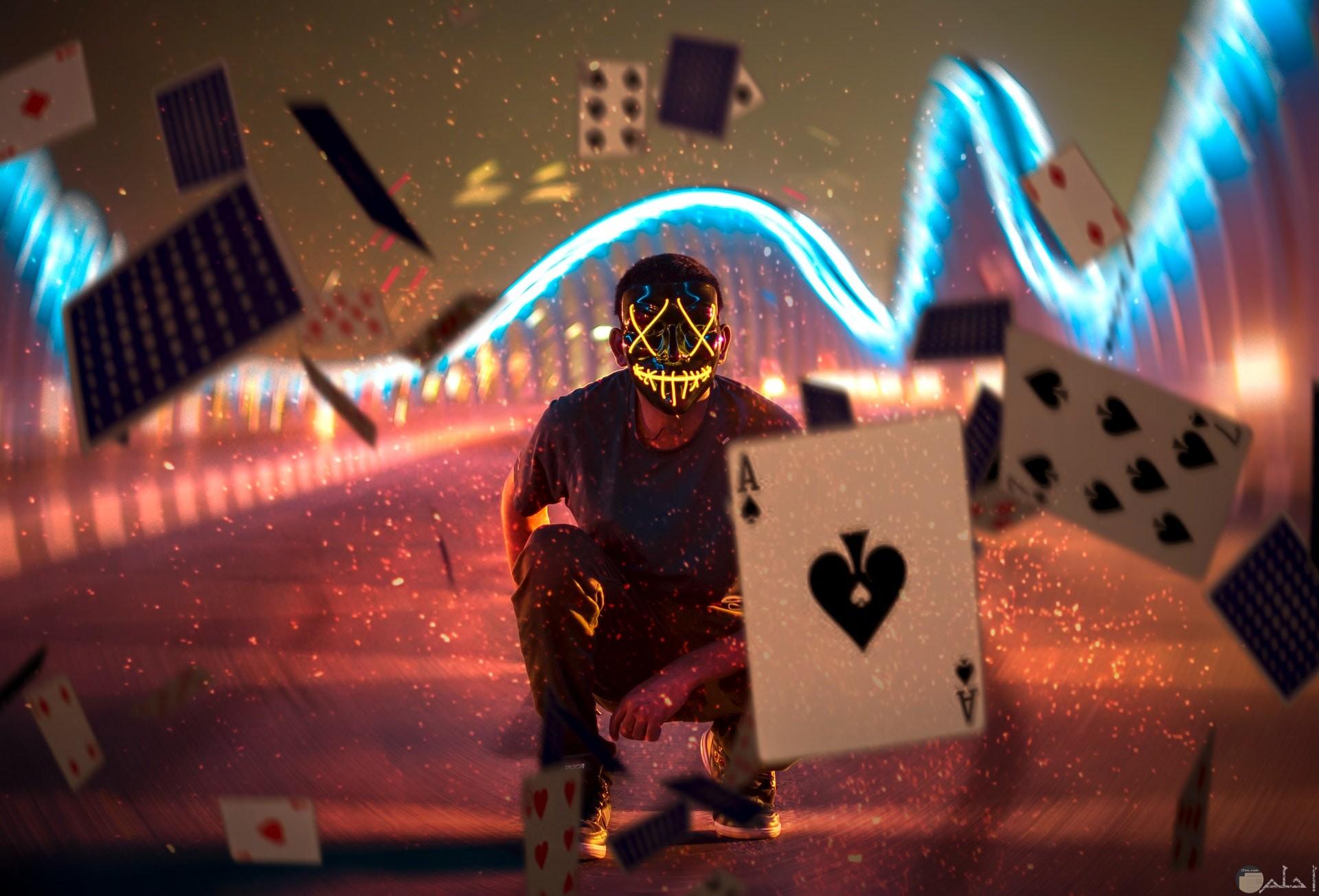 صورة أكشن رعب لشاب يرتدي قناع مخيف مع مجموعة أوراق متطايرة وأضواء في الخلفية