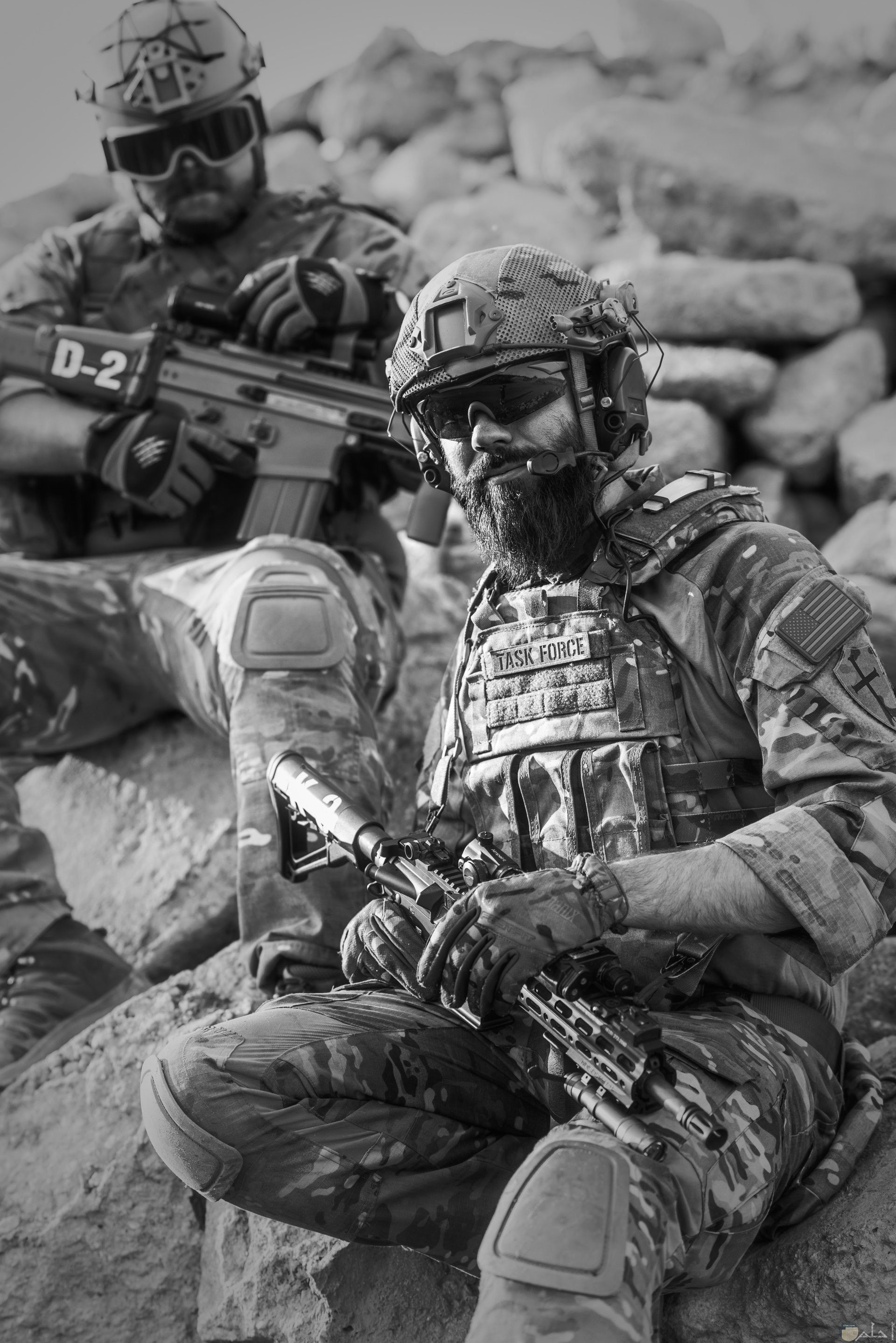 صورة أكشن مميزة بالأبيض والأسود لمجندين يحملان سلاح ويجلسان علي الصخر