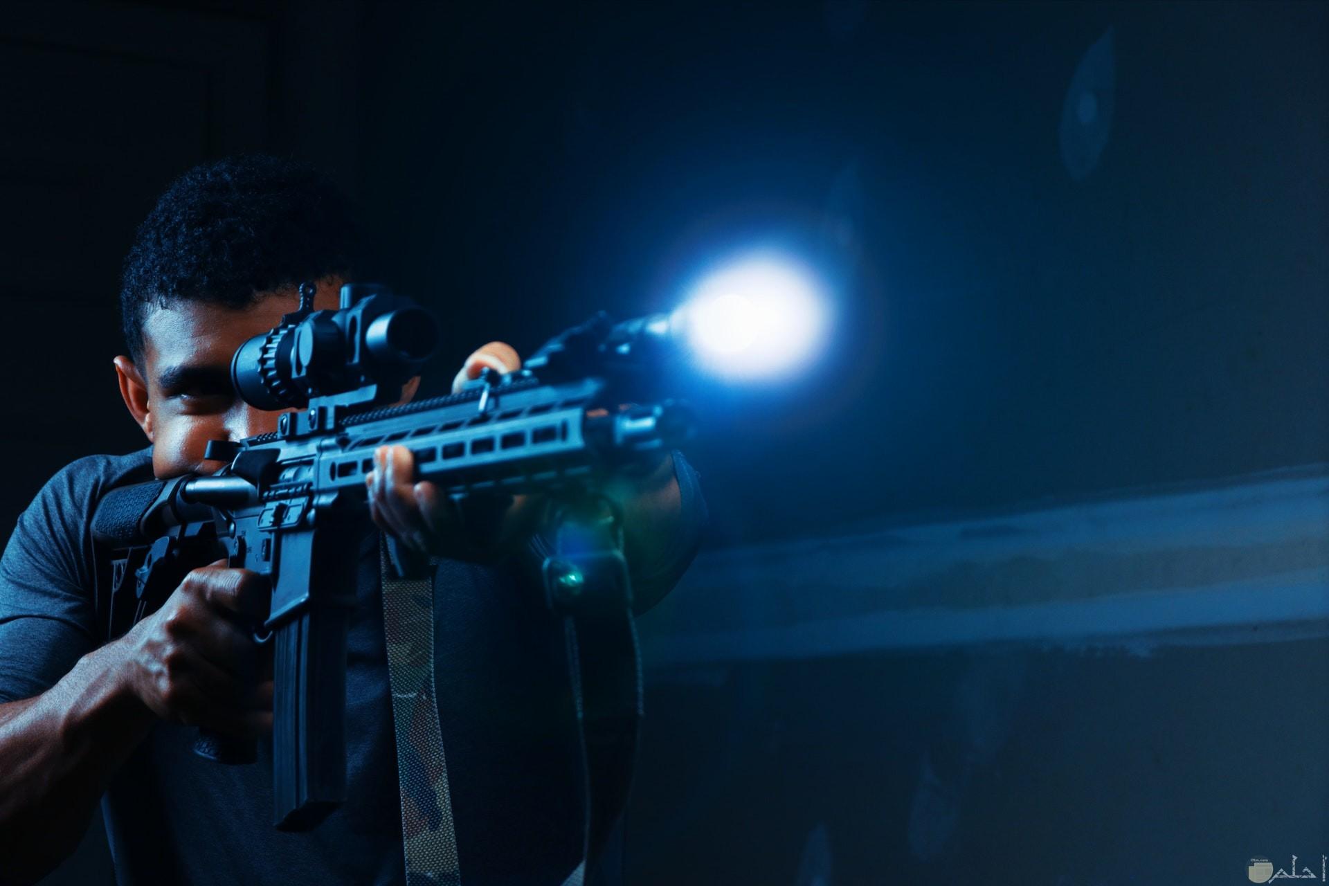 صورة أكشن مميزة لشاب يحمل سلاح في الظلام