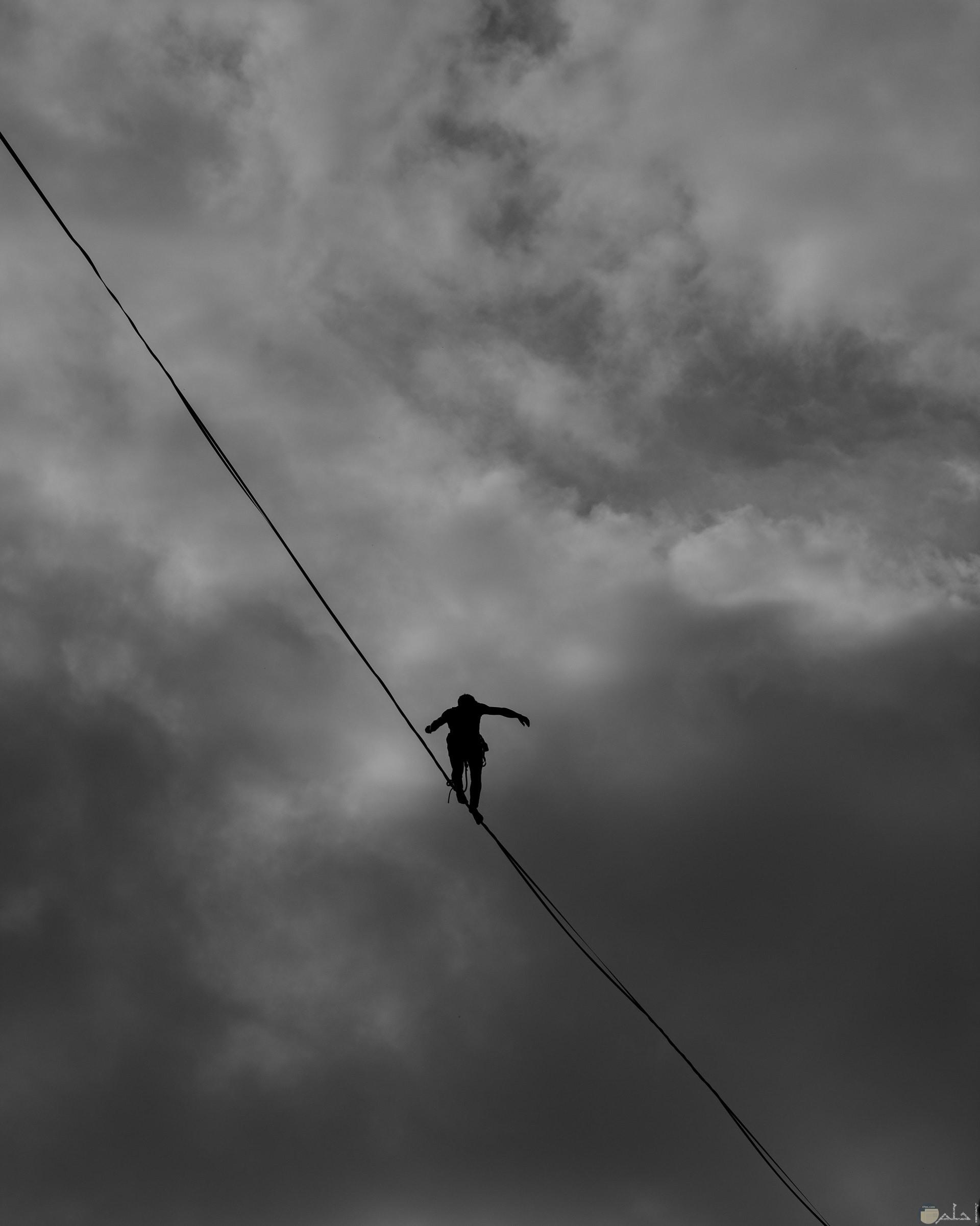 صورة أكشن مميزة لشاب يمشي علي حبل علي إرتفاع عالي