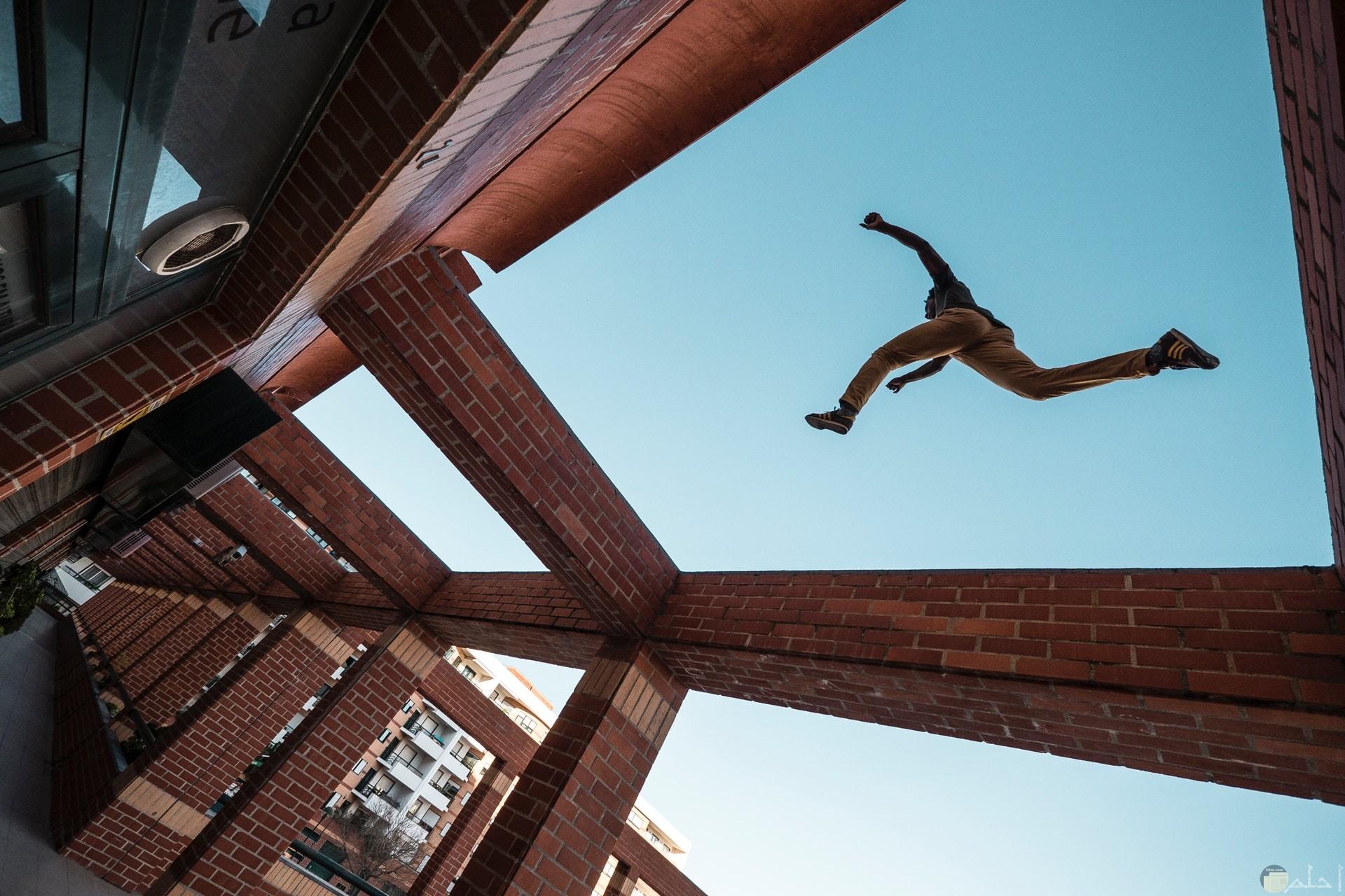 صورة أكشن مميزة لشخص يقفز عاليا من نقطة لنقطة أخري فوق مبني
