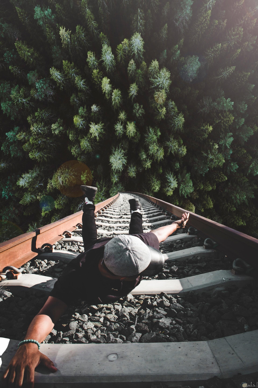 صورة أكشن مميزة لشخص يمثل أنه سيقع وممسك بأحد قطبان سكة القطار وتحته غابة كبيرة