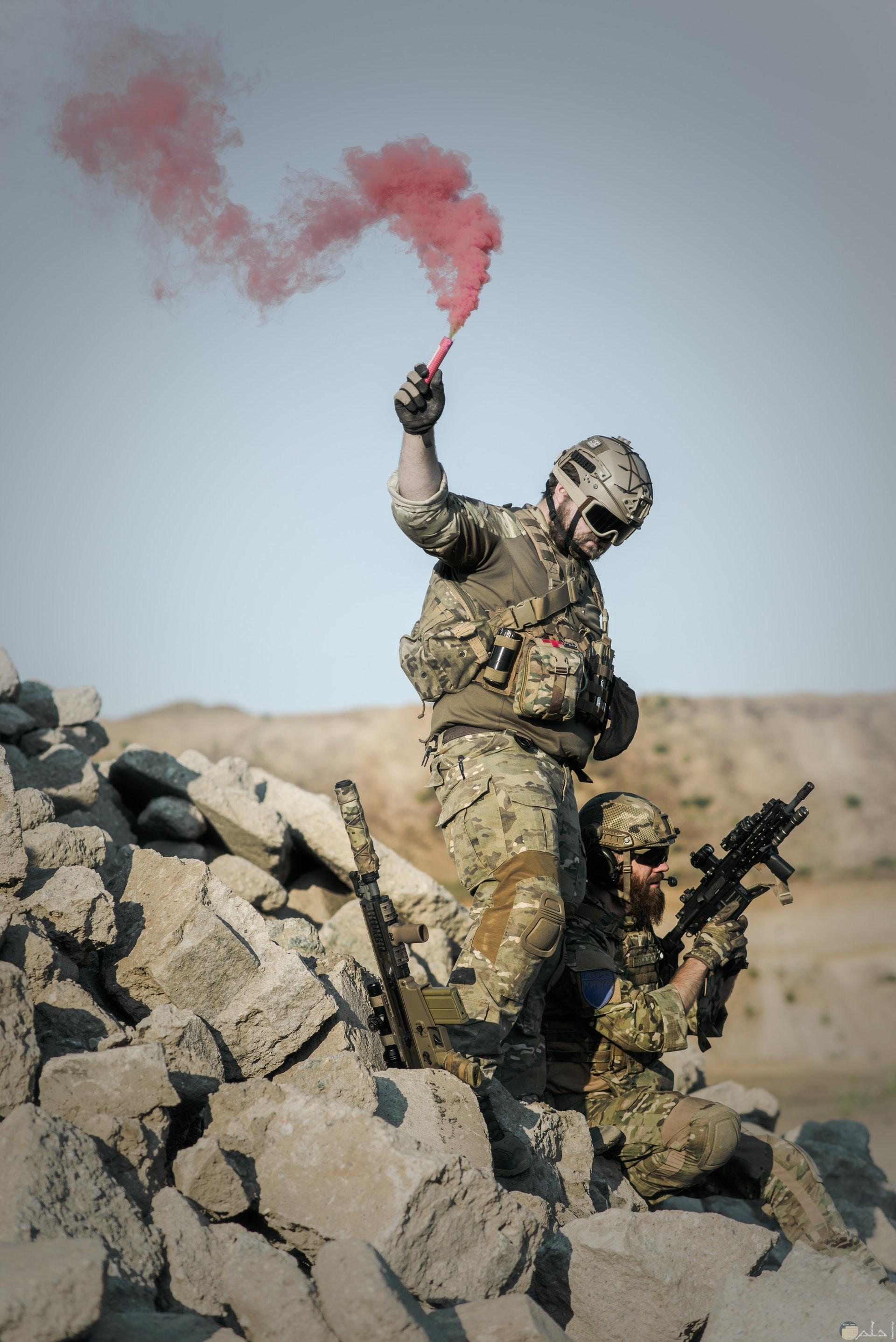 صورة أكشن مميزة لمجندين الأول جالس والثاني واقف وبجانبه سلاحه