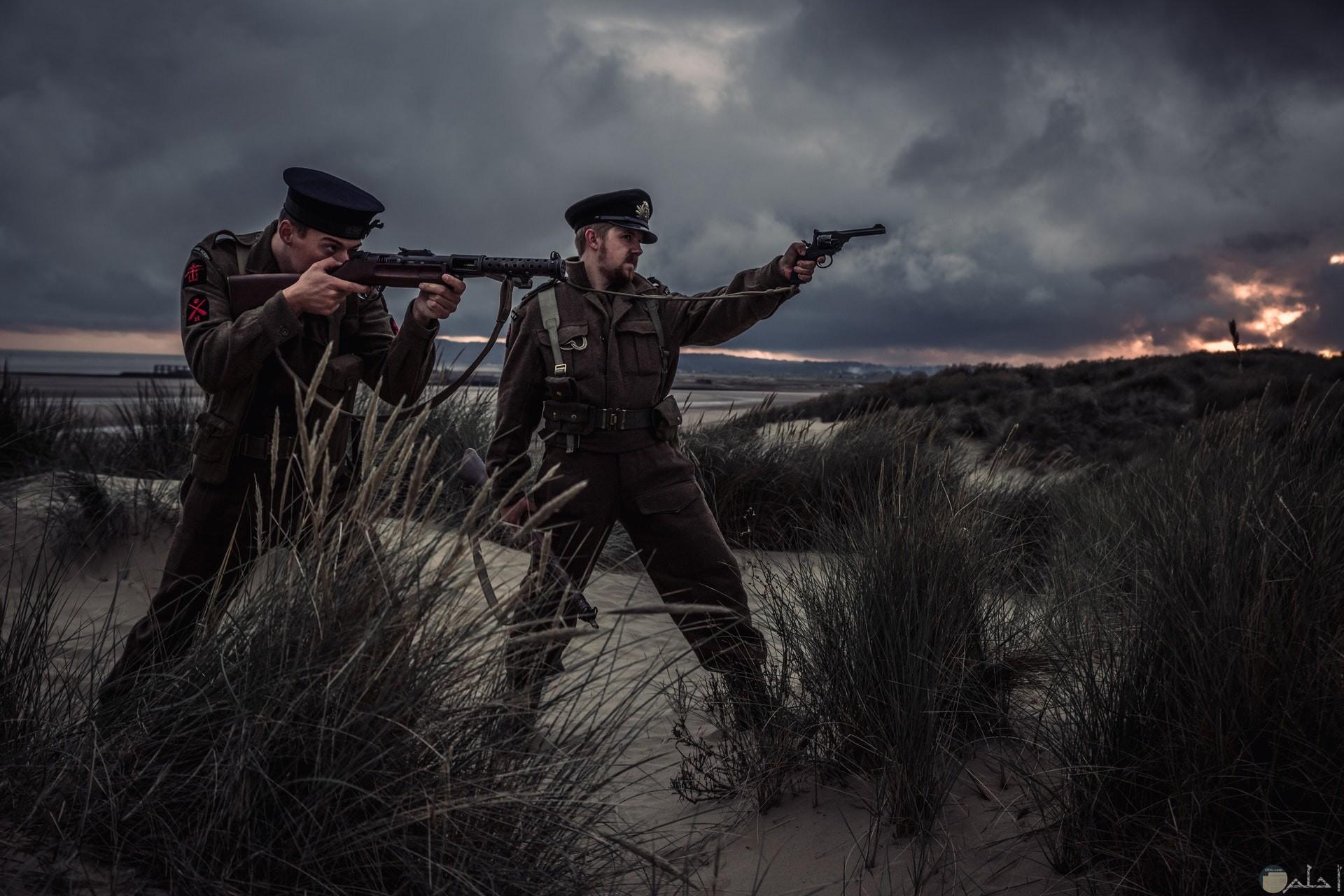 صورة أكشن مميزة لمجندين يحملان سلاح وواقفان للتصويب علي شيء ما والسماء ممتلئه بالغيوم