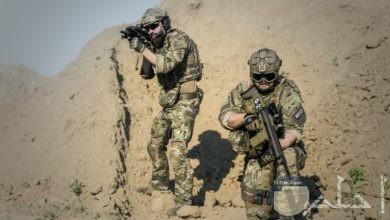 صورة أكشن مميزة لمجندين يحملان سلاح وواقفان يراقبان شيء ما في الصحراء