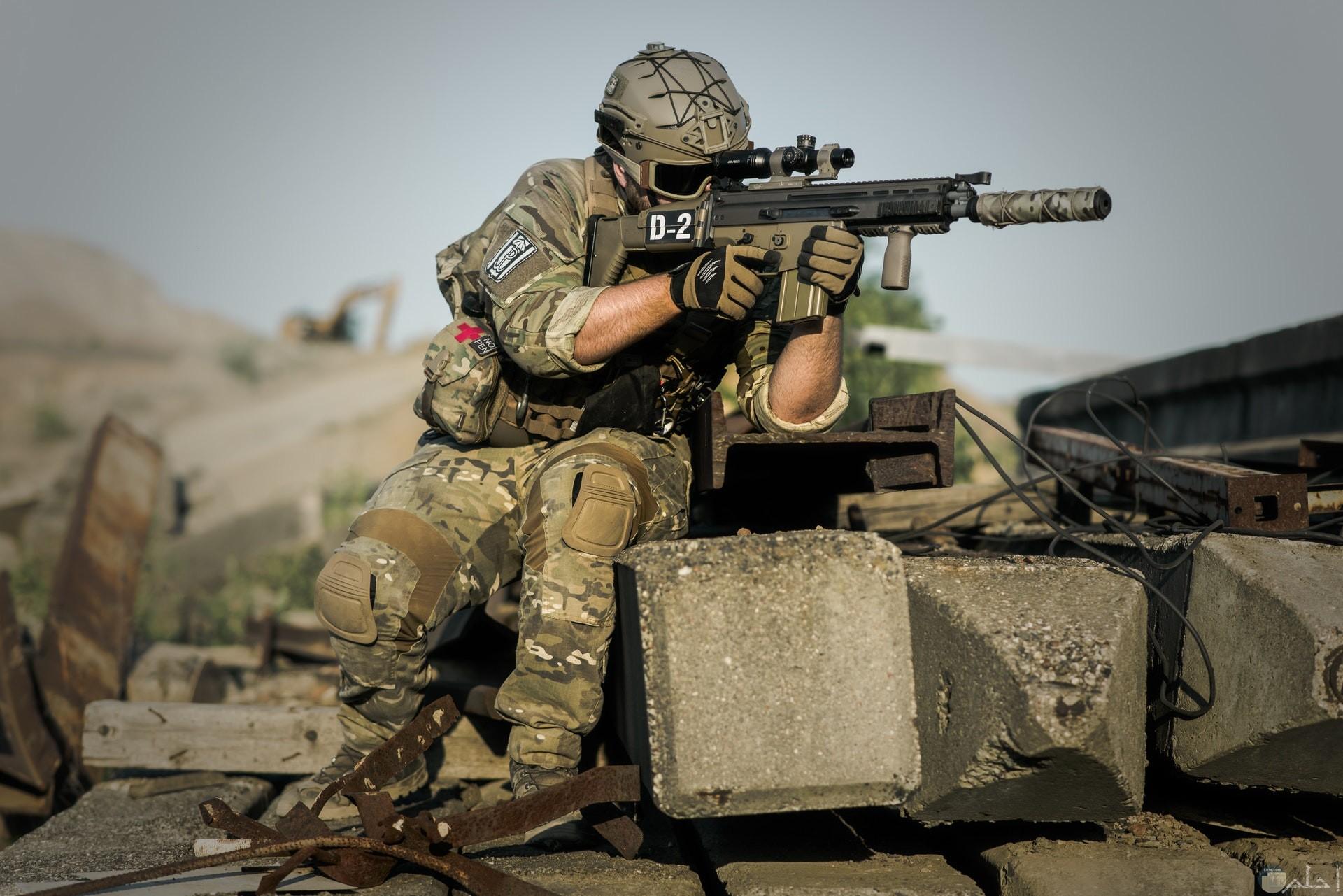 صورة أكشن مميزة لمجند يحمل سلاح وجالس فوق صخرة