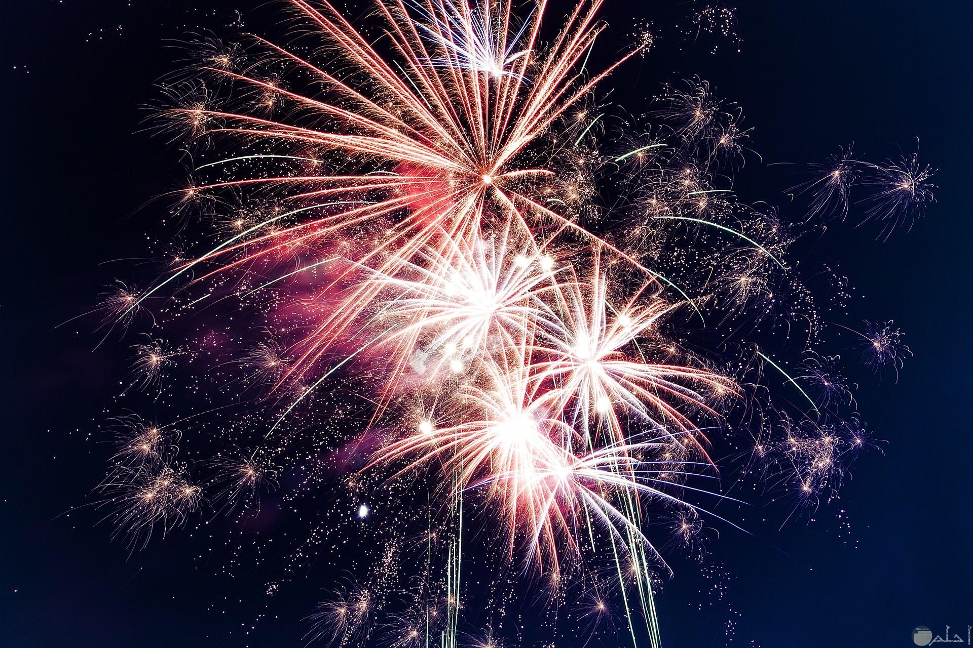 صورة ألعاب نارية حلوة في السماء في المساء بألوان الأبيض والأحمر