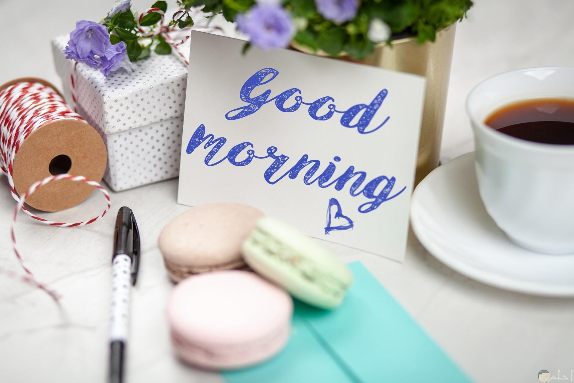 صورة تحية الصباح بالإنكليزي مكتوبه بلون بنفسجي مميز مع حلويات لذيذة
