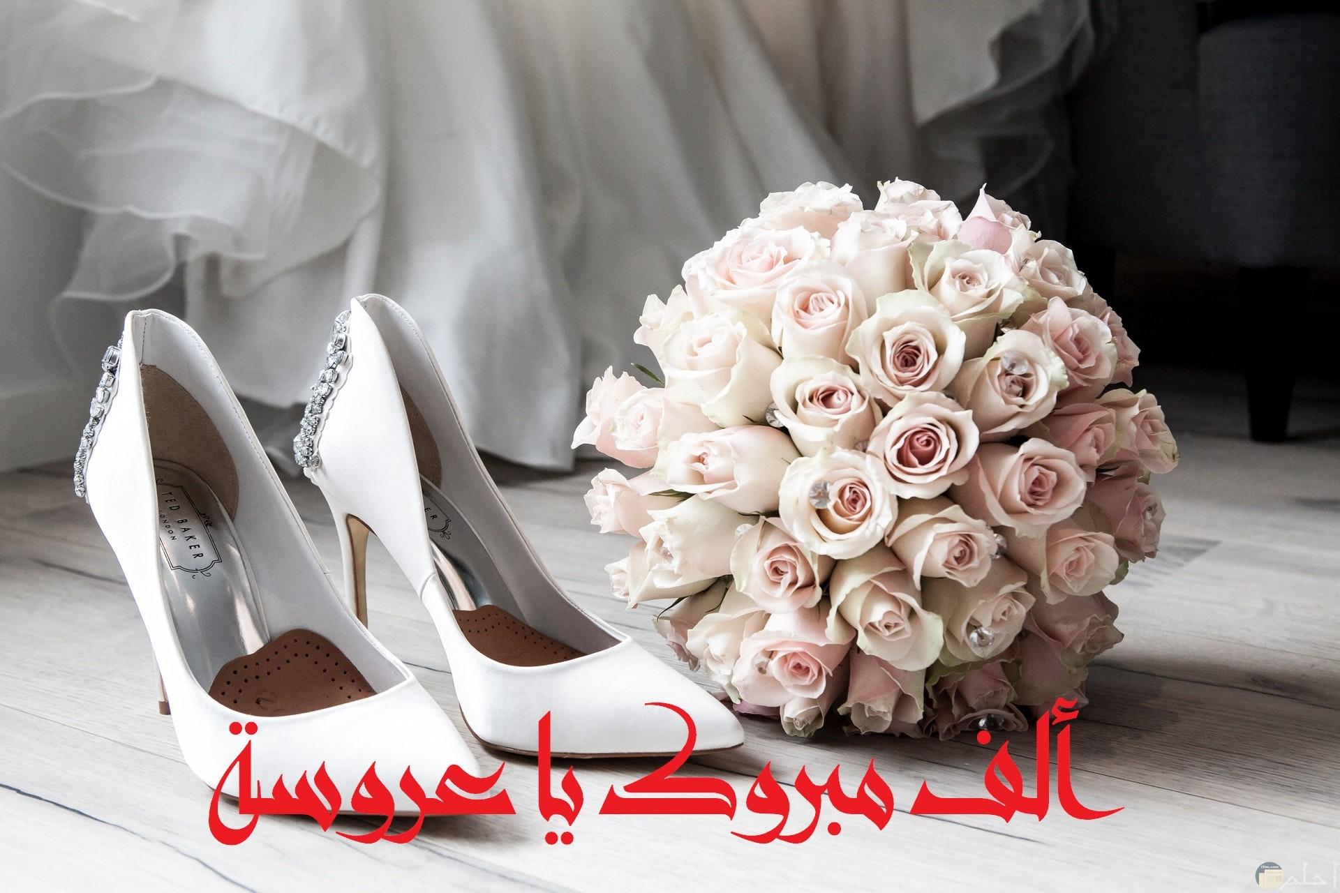صورة تهنئة بمناسبة الفرح جميلة جدا مكتوب عليها ألف مبروك يا عروسة وبوكيه ورد وحذاء أبيض وفستان حلو في الخلف