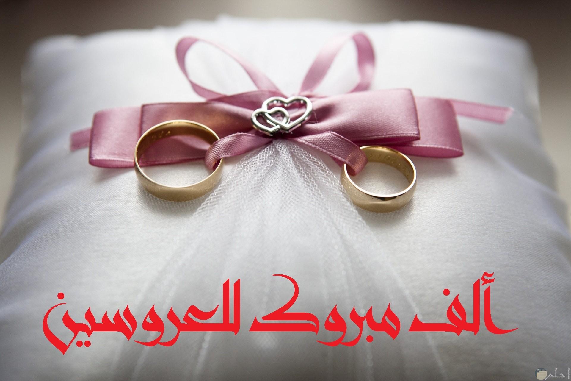 صورة تهنئة جميلة جدا بمناسبة الزواج مكتوب عليها ألف مبروك للعروسين بخط مميز مع خاتمين