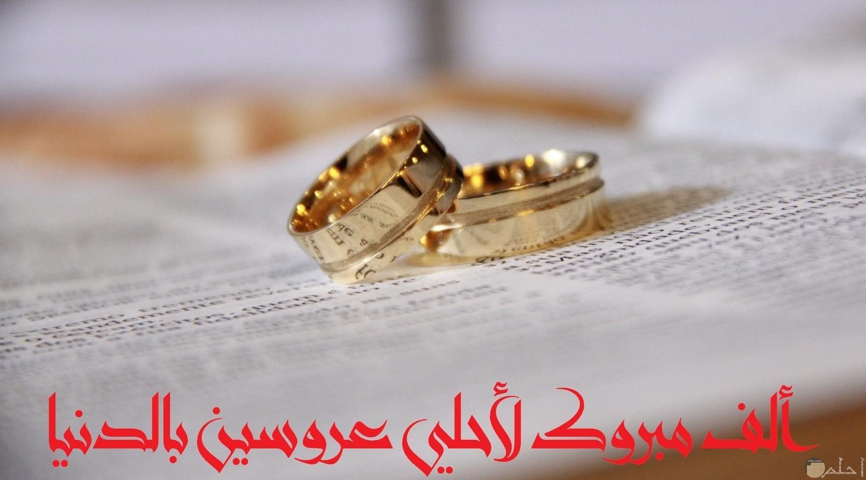 صورة تهنئة جميلة مكتوب عليها ألف مبروك لأحلي عروسين بالدنيا مع خاتمين حلوين