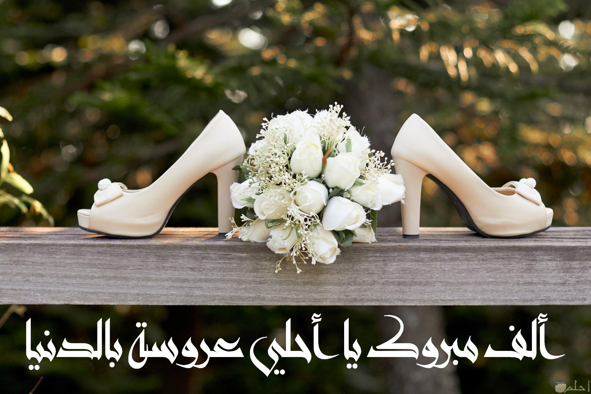 صورة تهنئة جميلة جدا مكتوب عليها ألف مبروك يا أحلي عروسة بالدنيا مع بوكيه ورد وحذاء أبيض حلو ومميز