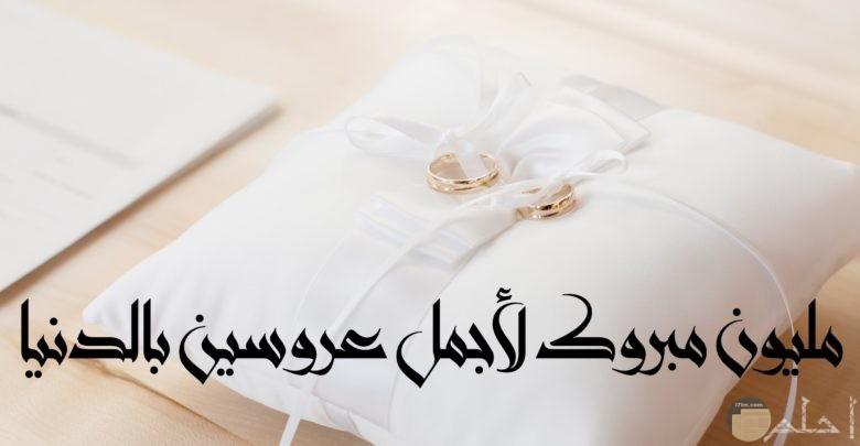 صورة تهنئة جميلة جدا مكتوب عليها مليون مبروك لأجمل عروسين بالدنيا مع خاتمين علي وسادة بيضاء