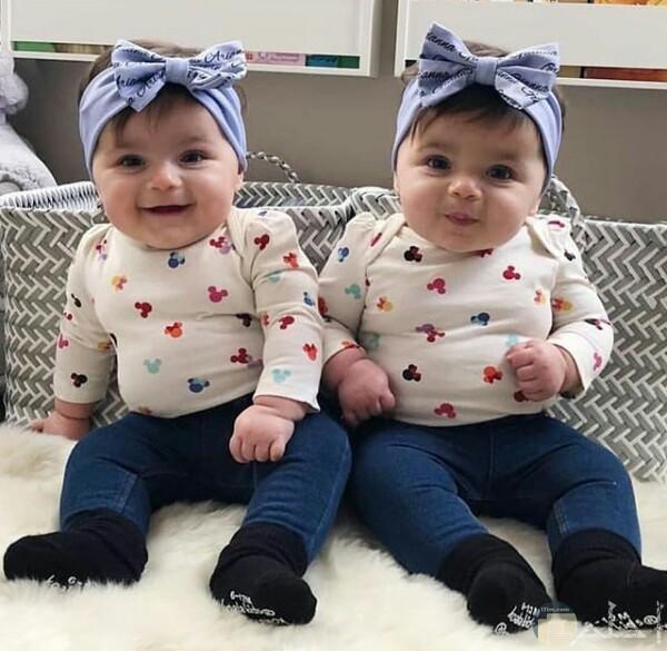 صورة جميلة جدا حول توائم بنات أطفال حلوين جالسين و مرتديين نفس الملابس