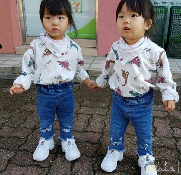 صورة جميلة جدا حول توائم بنات اطفال حلوين لابسين نفس اللبس واقفين في الشارع