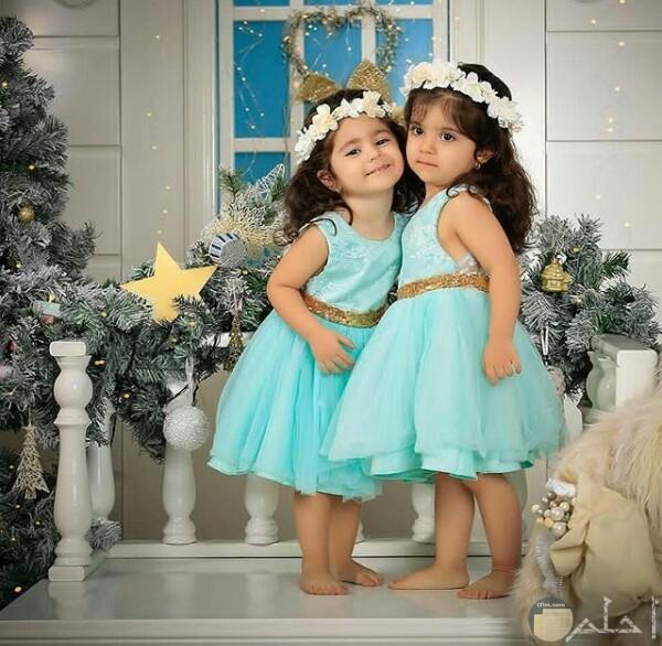 صورة جميلة جدا لبنتين صغار ترتدي كل منهن فستان لبني حلو مع طوق من الورد علي رأسيهما