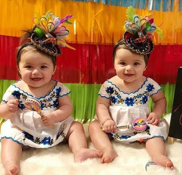 صورة جميلة جدا لبنتين صغار جالسين علي الأرض ولابسين نفس الفستان الحلو