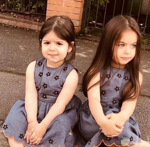 صورة جميلة جدا لبنتين صغيرتين جالستان علي الأرض بفستان حلو